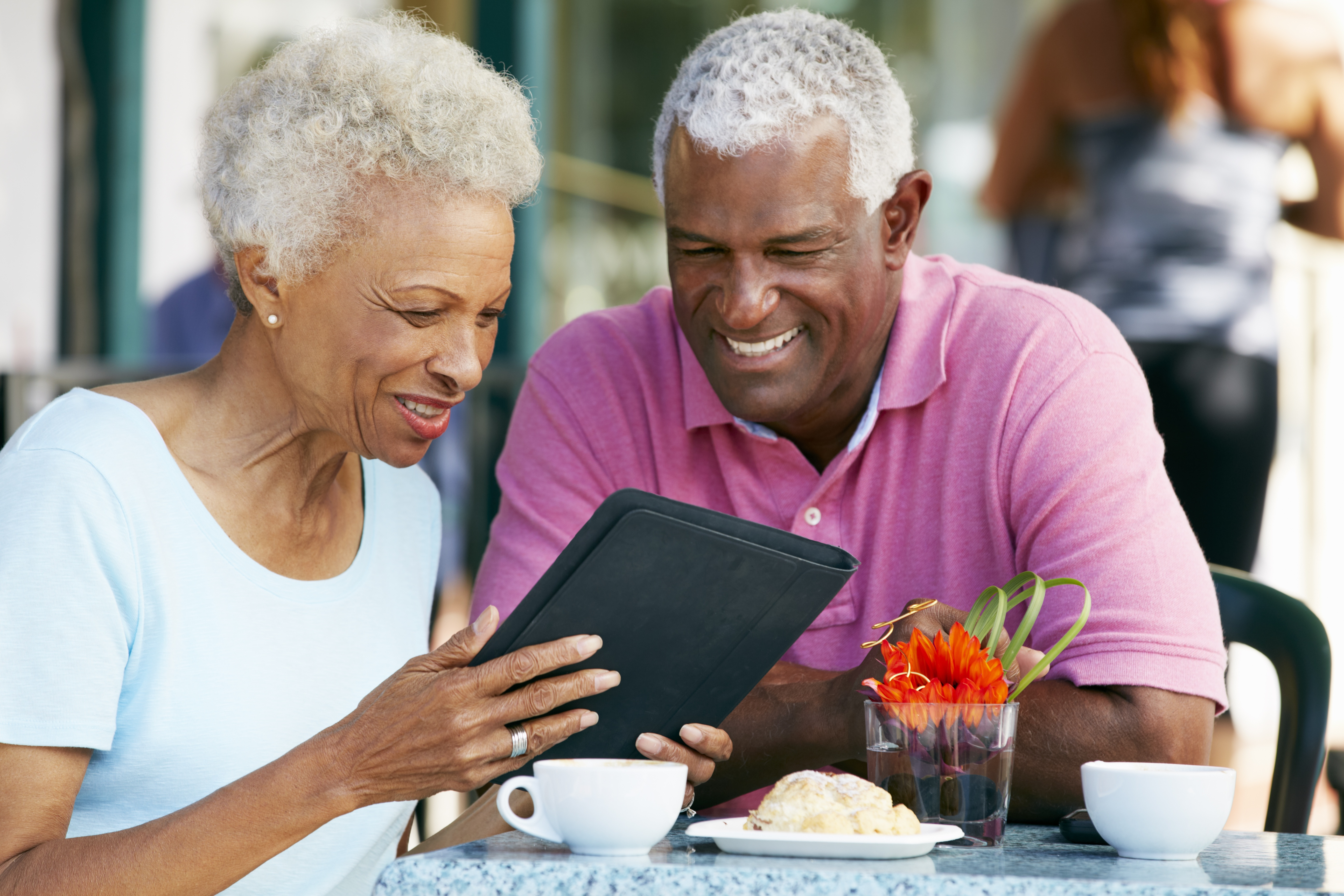 African American couple holding tablet